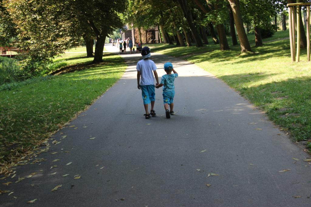 Geschwister spazieren Hand in Hand durch den Tierpark