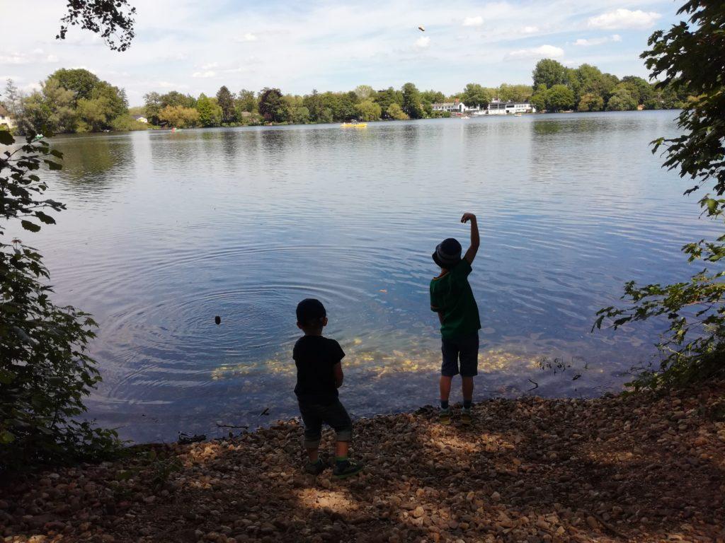 Zwei Brüder an einem See beim Steine ins Wasser werfen