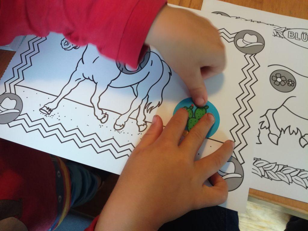 Kind klebt Sticker an gekennzeichneter Stelle auf dem Bild auf
