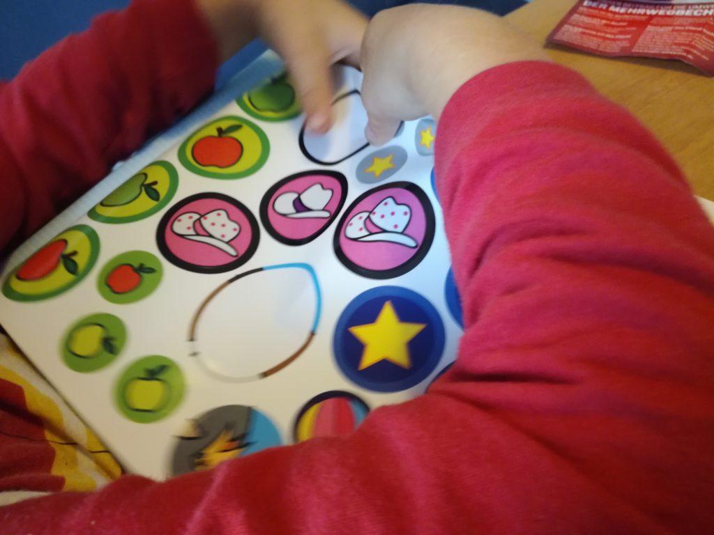 Kind sucht sich die passenden Sticker zum Aufkleben aus